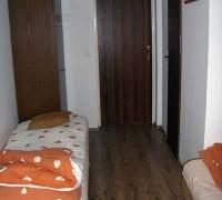 Widok na łóżko jednoosobowe i wyjście z pokoju na korytarz
