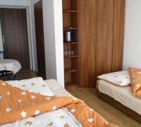 Widok na przestronną szafę, wygodne łóżka Ośrodka Delfin Mrzeżyno i wejście do łazienki z prysznicem i umywalką